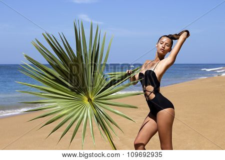 Fashion beautiful woman in bikini with palm branch on beach near sea enjoying sun. Hair up.Tropics.H