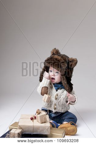 Funny Baby In A Winter Fur Hat With Gift Boxes Over Gray Background.