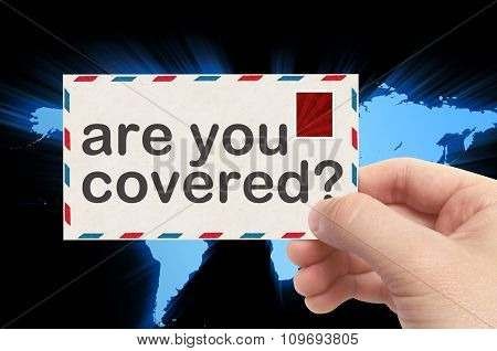 Hand Holding Envelope With Are You Covered? Word And World Background