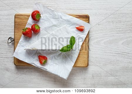 Brie Triangle With Fresh Strawberries On Craft Paper White Table