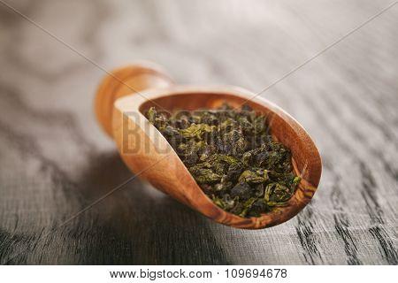 oolong green tea in wood bowl on oak table