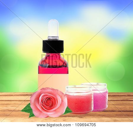 Bottle With Essence Oil And Rose Flowers On Wooden Table Over Nature Background