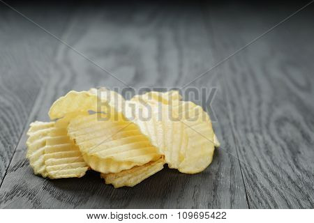 salted potato ships on old wooden table