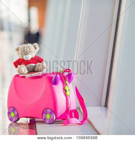 Closeup pink small kids suitcase in airport near window