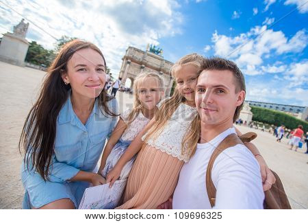 Happy young family with map of city taking selfie background famous Louvre in Paris