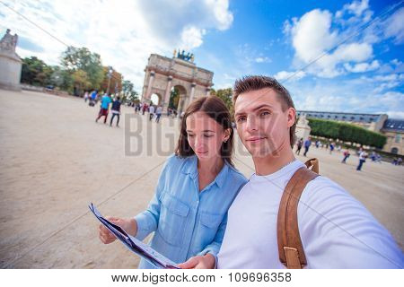 Romantic young couple with map of city taking selfie background famous Louvre in Paris