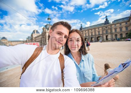 Romantic young couple with map of city taking selfie background famous Louvre