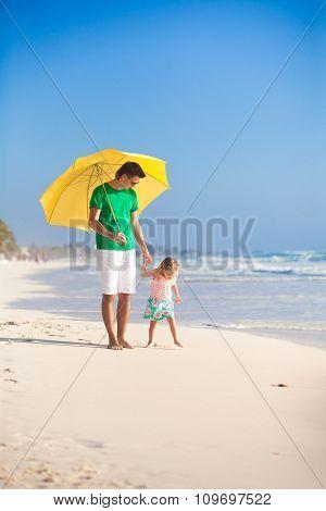 Happy family under yellow umbrella on white sandy beach