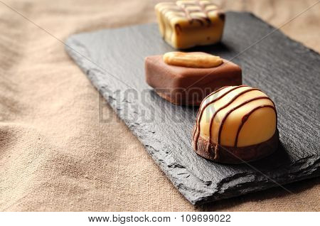 Assorted Bonbons On A Slate Plate Close Up