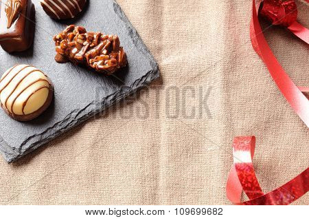 Assorted Bonbons On A Slate Plate With Red Ribbon Top
