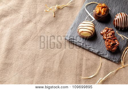 Assorted Bonbons On A Slate Plate With Straw Decoration Top