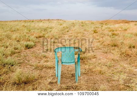 Grungy Retro Damaged Plastic Green Chair Abandoned In A Field