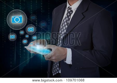 Businessman hand touch camera icons on a tablet.