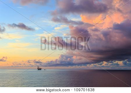 Offshore Jack Up Drilling Rig In The Middle Of The Ocean During Sunset Time
