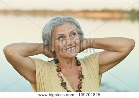 Elderly woman near lake
