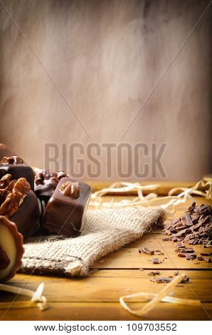 Bonbons Stacked On Burlap Sack On Wood Table Vertical Composition