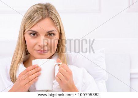 Young woman enjoying hot drink.