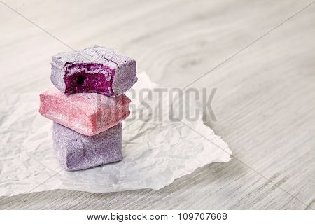 Set Of Three Pastel Colored  Square Marshmallows On Craft Paper, Bite