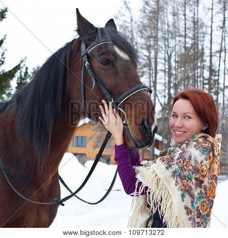 Portrait of red hair young woman at shawl with horse in winter