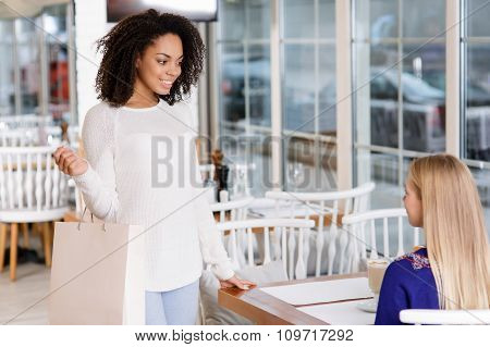Young woman meets her friend at the restaurant.
