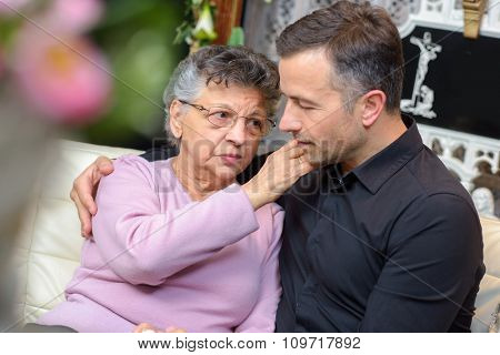 Man and elderly lady comforting each other