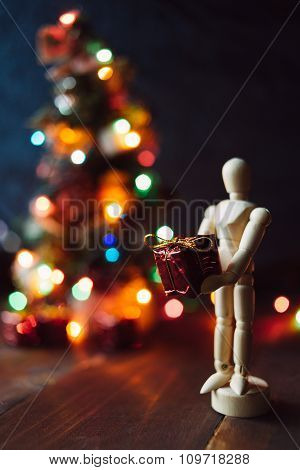 Wooden Mannequin With The Gift And The Chritsmas Tree
