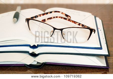 Glasses, Books And Notebook On The Table Surface.