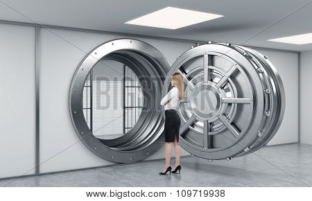 Young Lady Standing In Front Of A Big Unlocked Round Metal Safe In A Bank Depository With Her Back H