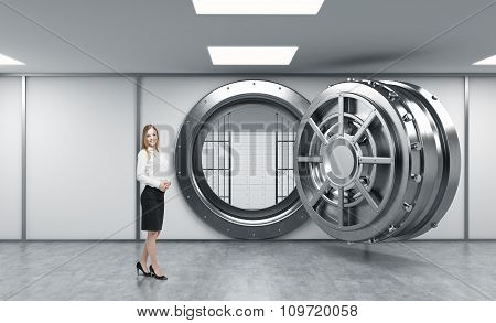 Smiling Young Lady Standing In Front Of A Big Unlocked Round Metal Safe In A Bank Depository With Lo