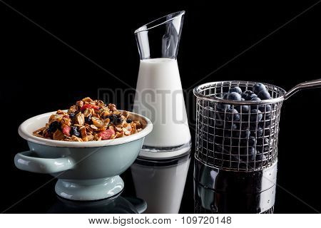 Blueberries granola and yogurt on black from side