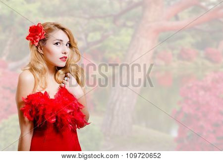 Beautiful young woman in red dress on garden blossom background