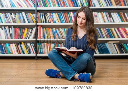 Smiling Young Girl  Sitting On The Floor In The Library Reading An Open Book On Her Knees, Left-cent