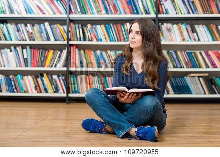 Smiling Young Girl  Sitting On The Floor In The Library With An Open Book On Her Knees Looking Sidew