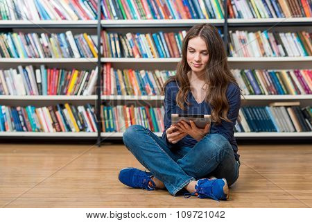 Smiling Young Girl Sitting On The Floor In The Library With Crossed Legs, Slightly Turned To The Rig