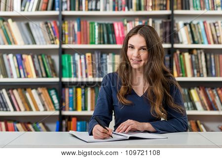 Smiling Young Girl With Loose Long Dark Hair  Sitting At A Desk In The Library With An Open Note Boo