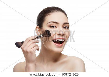 Beautiful happy girl applying blush with brush