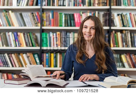 Smiling Young Girl With Dark Hair  Sitting At A Desk In The Library With An Open Note Book Writing O