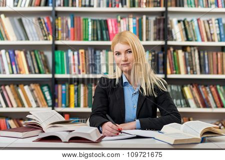 Smiling Young Girl With Blonde Hair Sitting At A Desk In The Library With An Open Note Book Writing