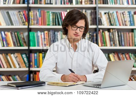 Serious Young Man With Dark Hair Sitting At A Desk In The Library Making Notes, Laptop And Organiser