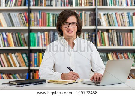 Smiling Young Man With Dark Hair  Sitting At A Desk In The Library Making Notes, Laptop And Organise