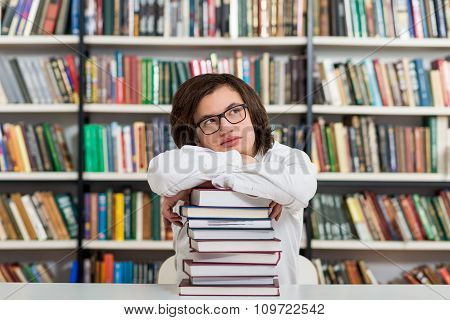 Young Man Sitting At A Desk In The Library With His Arms On A Big Pile Of Books And Chin On Them, He