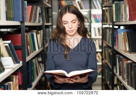 Serious Young Girl With Loose Long Dark Hair Standing And Holding An Open Book Between Book Shelves
