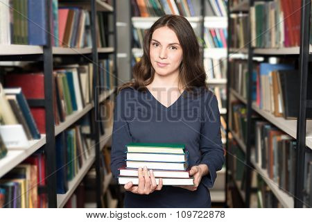 Smiling Young Lady With Loose Dark Blonde Hair Standing And Holding A Pile Of Books Between Book She