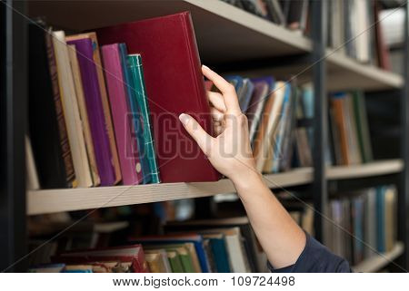 A Book Picked Or Taken With A Hand From A Book Shelf In The Library, A Concept Of Learning And Choic