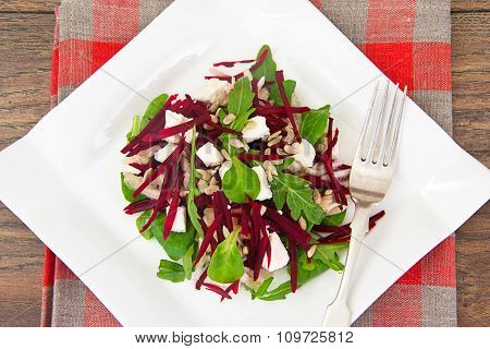 Salad of raw beets, pears, arugula, roots, sunflower seeds and c