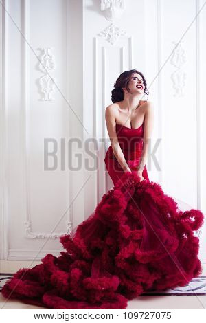 Beauty Brunette model woman in  evening red dress. Beautiful fashion luxury makeup and hairstyle,