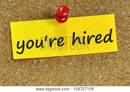 You're Hired Word On Yellow Notepaper With Cork Background