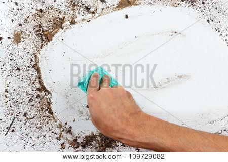 Hand with cloth cleans dirty surface
