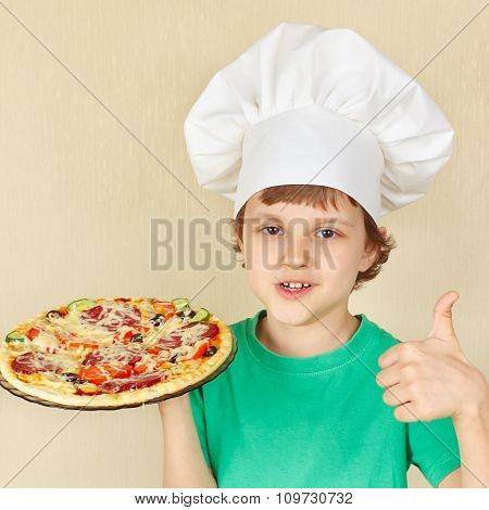 Young smiling boy in chefs hat with cooked appetizing pizza