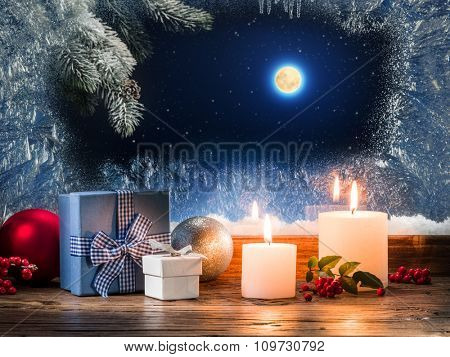 Christmas presents with burning candle on the windowsill with pattern frost.